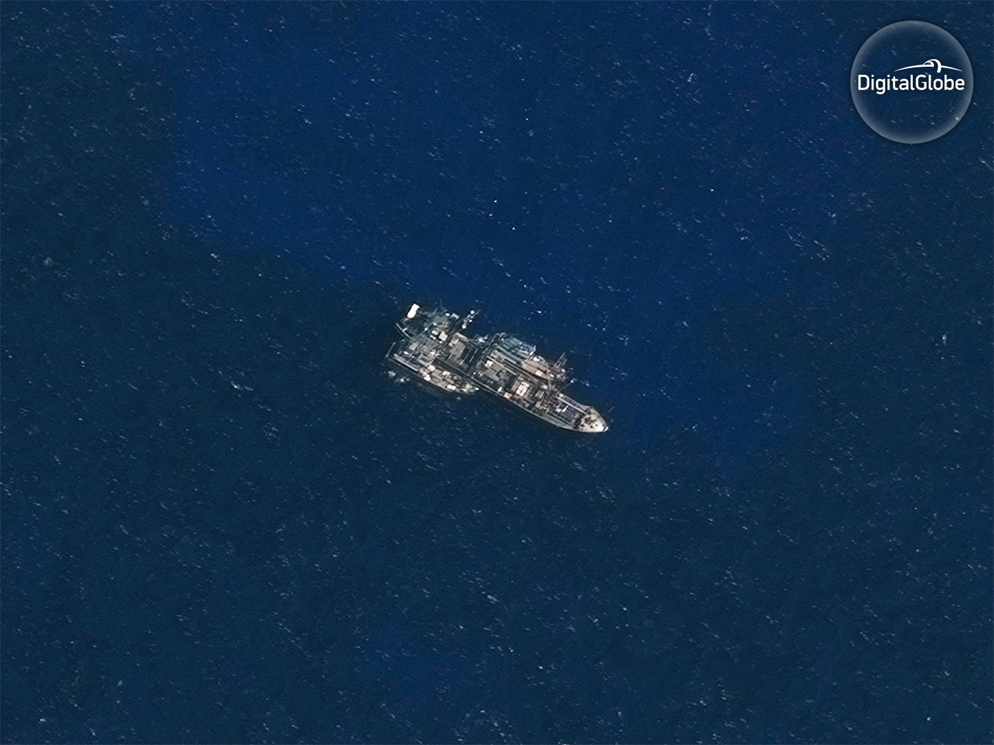 In the Indian Ocean, off the remote Saya de Malha bank, the refrigerated cargo vessel (reefer) Leelawadee was seen with two unidentified likely fishing vessels tied alongside. Image Captured by DigitalGlobe on Nov. 30, 2016. Credit: DigitalGlobe © 2017. Image by DigitalGlobe via SkyTruth.